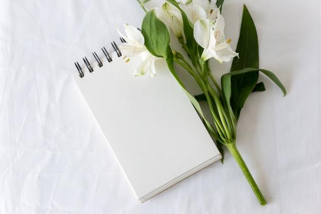 Hoge hoekmening van spiraalvormige blocnote met witte leliesbloem over witte achtergrond Gratis Foto