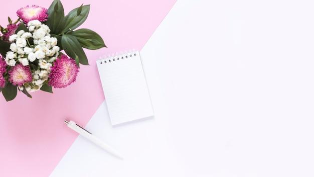 Hoge hoekmening van spiraalvormige blocnote; pen en bos bloemen op dubbele achtergrond Gratis Foto