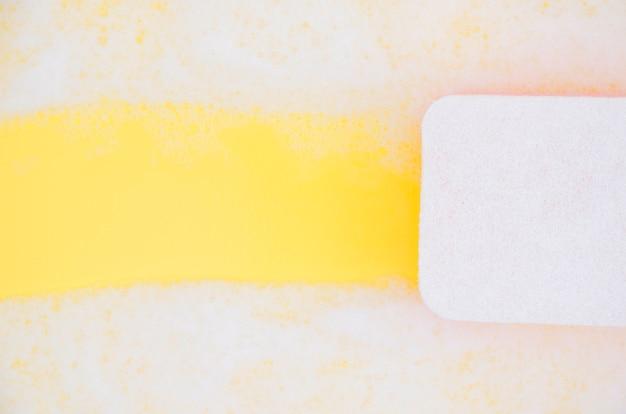 Hoge hoekmening van spons schoonmakende zeep sud op gele achtergrond Gratis Foto