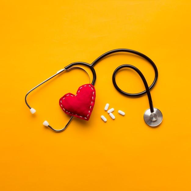 Hoge hoekmening van stethoscoop; gestikte hart en medicijnen over gele achtergrond Gratis Foto