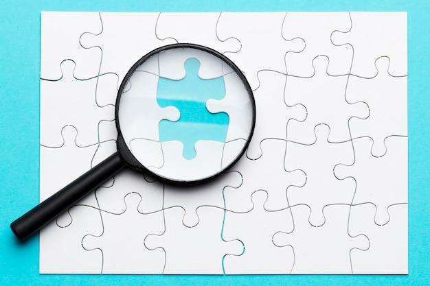 Hoge hoekmening van vergrootglas op ontbrekende puzzel over blauwe achtergrond Gratis Foto