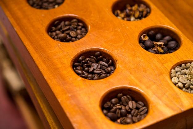 Hoge hoekmening van verschillende koffiebonen in houten container Gratis Foto