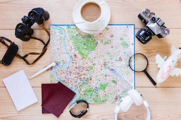 Hoge hoekmening van verschillende reizigerstoebehoren en kop thee op houten oppervlakte Gratis Foto