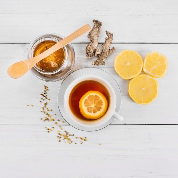 Hoge hoekmening van zoete honing; citroenthee en gember op houten achtergrond Gratis Foto