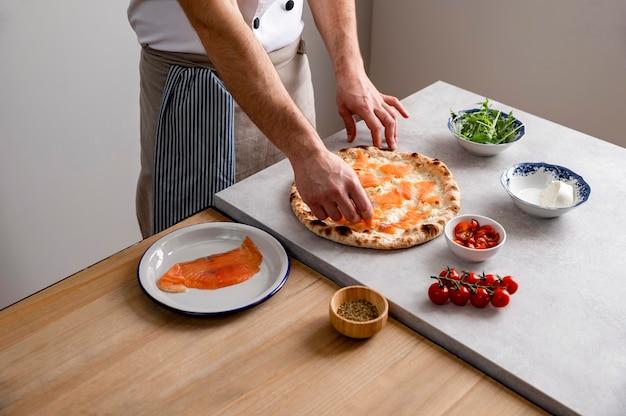 Hoge hoekmens die gerookte zalmplakken op gebakken pizzadeeg zet Gratis Foto