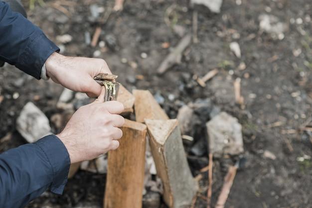 Hoge hoekmens die hout schikken voor vuur Gratis Foto