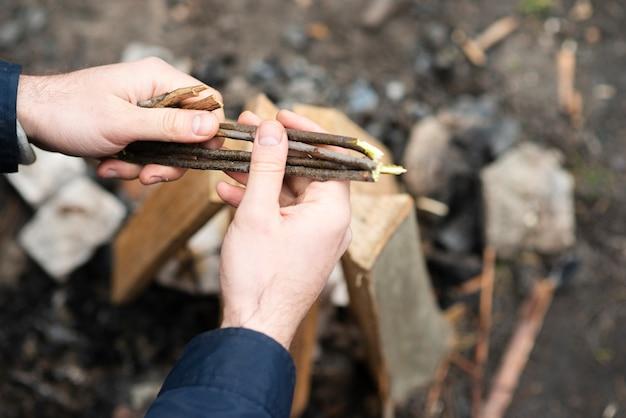 Hoge hoekmens die hout voorbereiden op vuur Gratis Foto