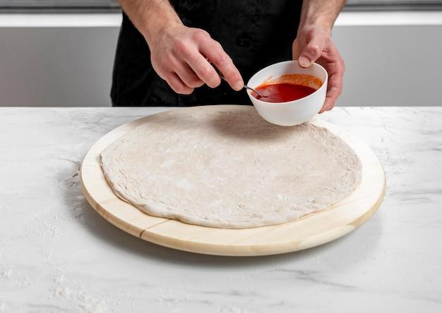 Hoge hoekmens die tomatensaus op pizzadeeg verspreidt Gratis Foto