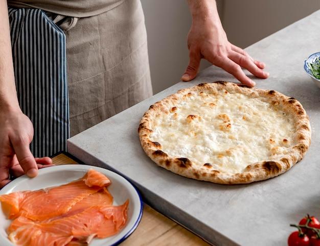 Hoge hoekmens die zich dichtbij gebakken pizzadeeg en gerookte zalmplakken bevindt Gratis Foto