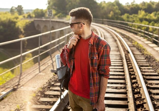 Hoge hoekmens met rugzak op treinspoor Gratis Foto