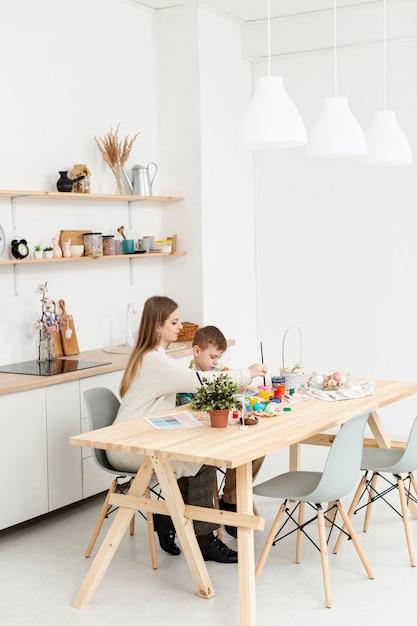 Hoge hoekmoeder en zoon die thuis eieren schilderen Gratis Foto