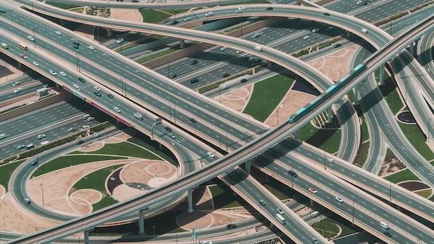 Hoge hoekopname van een grote snelweg met meerdere wegen en een trein die door de centrale weg rijdt Gratis Foto