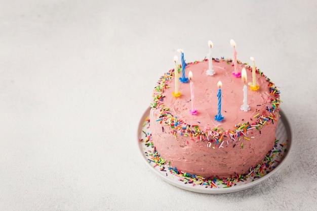Hoge hoekopstelling met roze cake voor verjaardagsfeestje Gratis Foto
