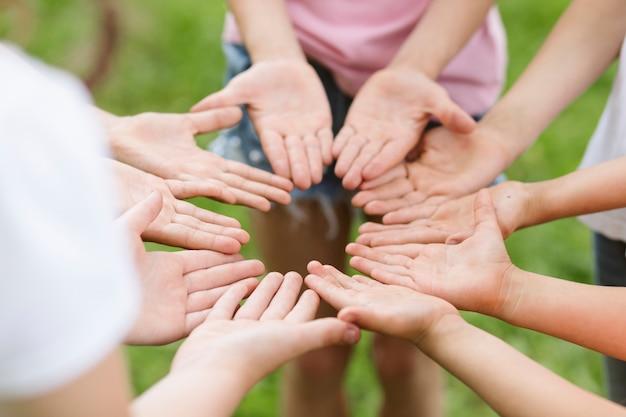 Hoge hoekvrienden die een bloem met hun handen maken Gratis Foto