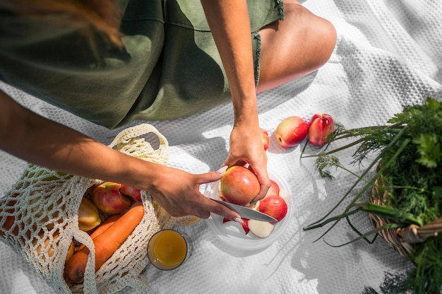 Hoge hoekvrouw die een picknick met gezonde snacks hebben Premium Foto