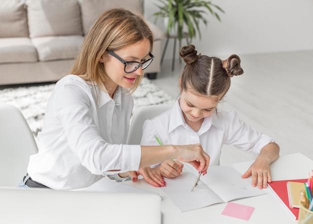 Hoge hoekvrouw die haar dochter met huiswerk helpt Gratis Foto