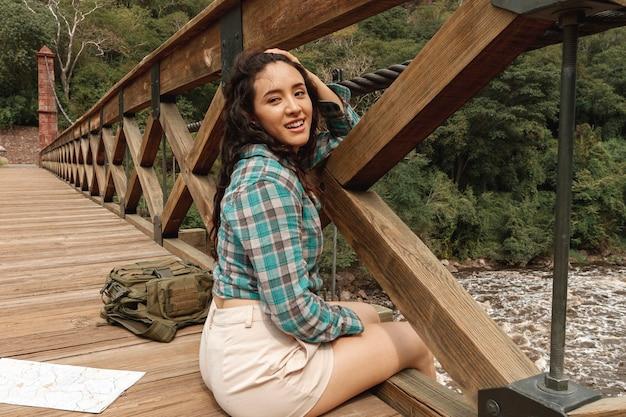 Hoge hoekvrouw die op brug rust Gratis Foto