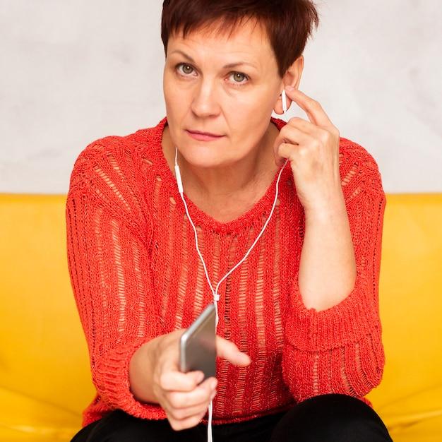 Hoge hoekvrouw op laag het luisteren muziek Gratis Foto