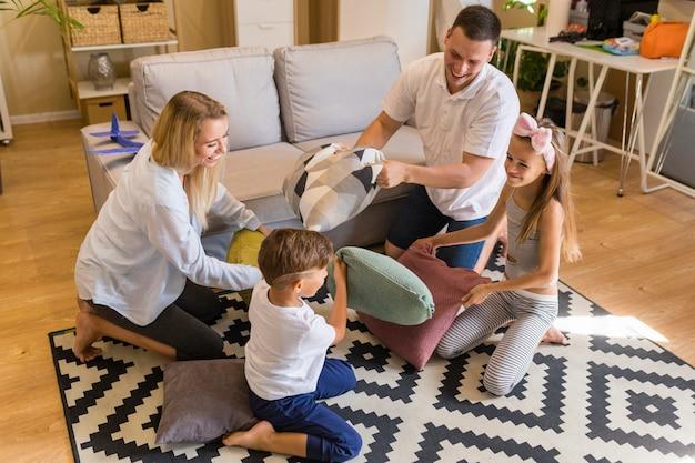 Hoge kijk familie spelen in de woonkamer met kussens Gratis Foto