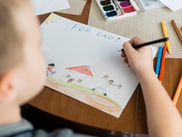 Hoge kijk kind en tekeningen voor zijn vader Gratis Foto