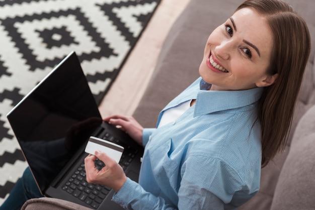 Hoge mening smileyvrouw die haar laptop met behulp van om online producten te kopen Gratis Foto