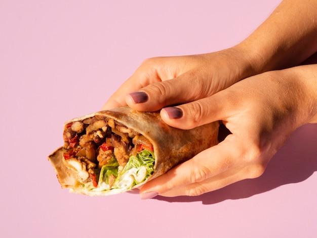 Hoge menings heerlijke mexicaanse taco die in handen wordt gehouden Gratis Foto