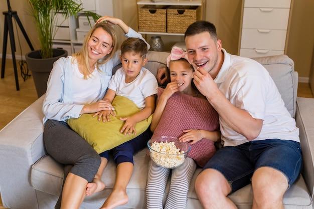 Hoge meningsfamilie die popcorn eet en op laag zit Gratis Foto