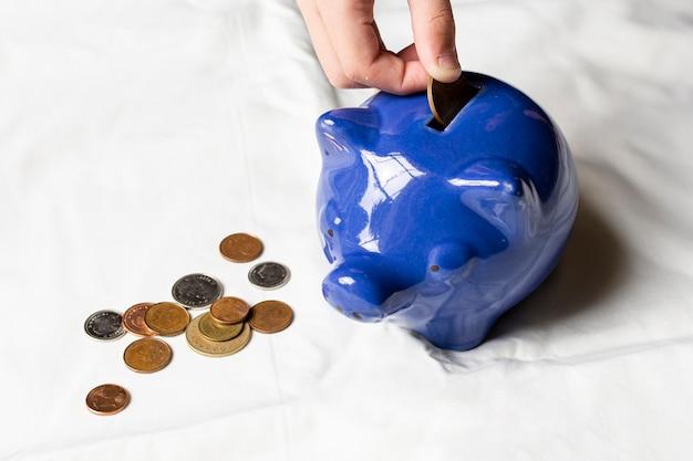 Hoge meningshand die muntstukken in een spaarvarken zet Gratis Foto