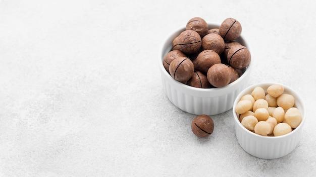 Hoge meningsmacadamia noten en chocolade in kommen Premium Foto