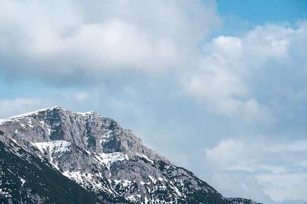 Hoge rotsachtige berg onder de bewolkte hemel Gratis Foto