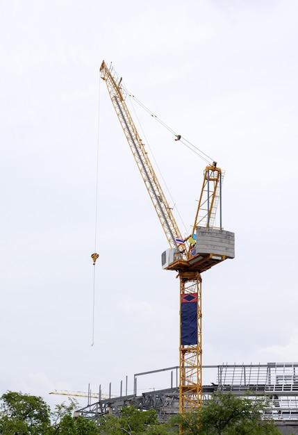 Hoge torenkraan op de bouwplaats voor de bouw van het grote overheidsgebouw in het stedelijk gebied. Premium Foto