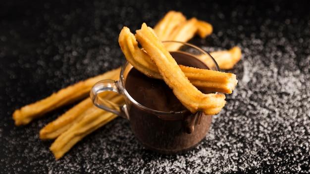 Hoge weergave churros en kopje gesmolten chocolade Gratis Foto