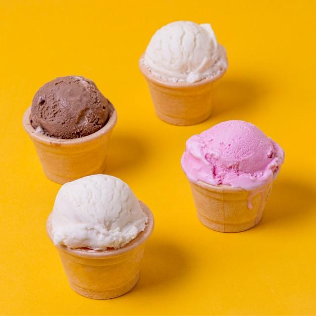 Hoge weergave verschillende ijssmaken in kegels Gratis Foto