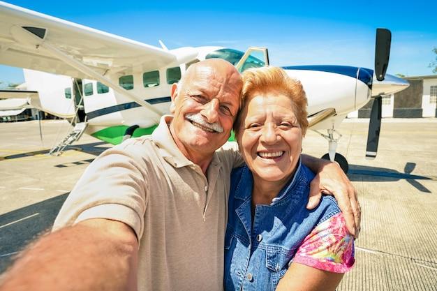 Hoger gelukkig paar die selfie met privé ultralight vliegtuig nemen voor reis rond de wereld Premium Foto