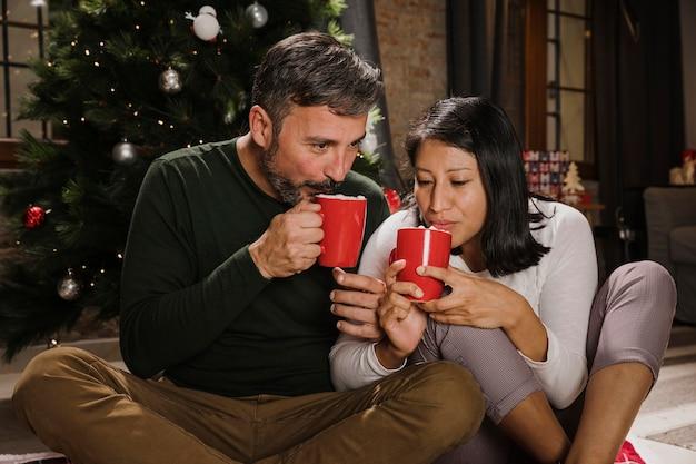 Hoger kerstmispaar die hete chocolade drinken Gratis Foto