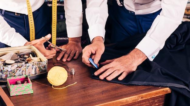 Hoger mannelijk kleermaker die doekpatroon met krijt op workshop merken Gratis Foto