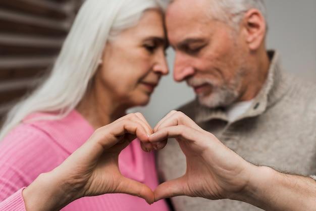 Hoger paar dat hartvorm van handen toont Gratis Foto