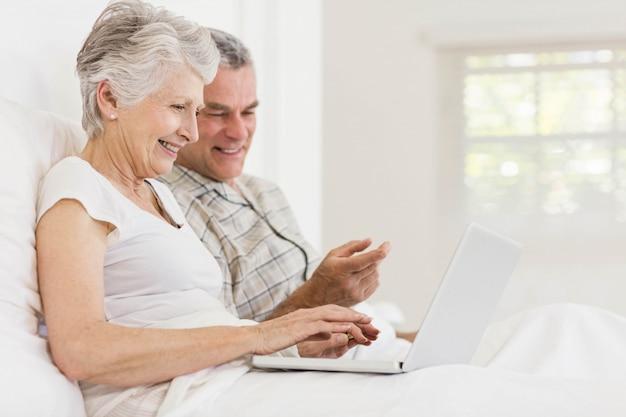 Hoger paar dat laptop zitting op het bed gebruikt Premium Foto