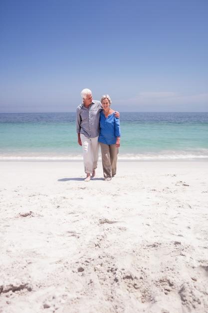 Hoger paar dat op het strand loopt Premium Foto