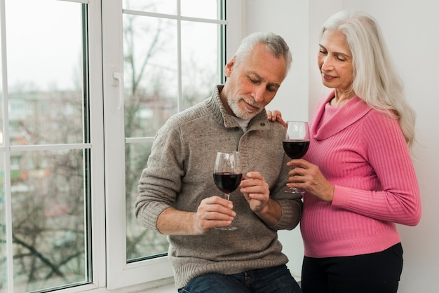 Hoger paar dat van glas wijn geniet Gratis Foto