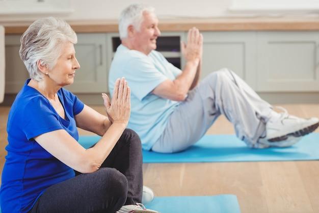 Hoger paar dat yogaoefening thuis uitvoert Premium Foto