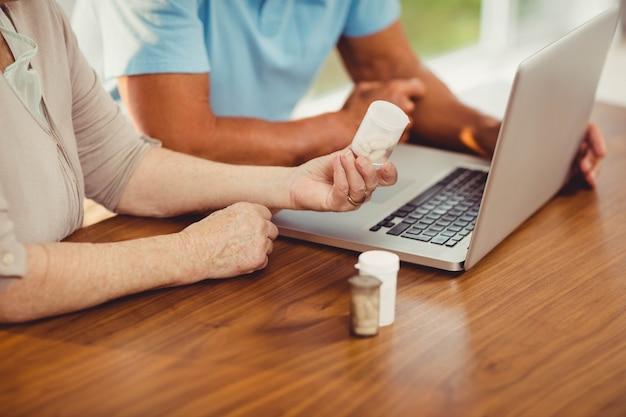Hoger paar gebruikend laptop en thuis houdend pillen Premium Foto