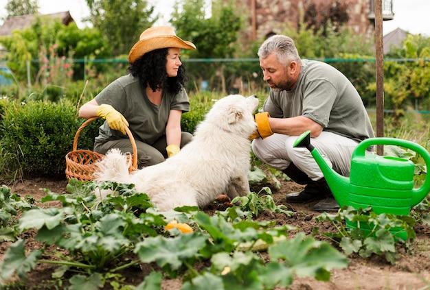 Hoger paar in tuin met een hond Gratis Foto