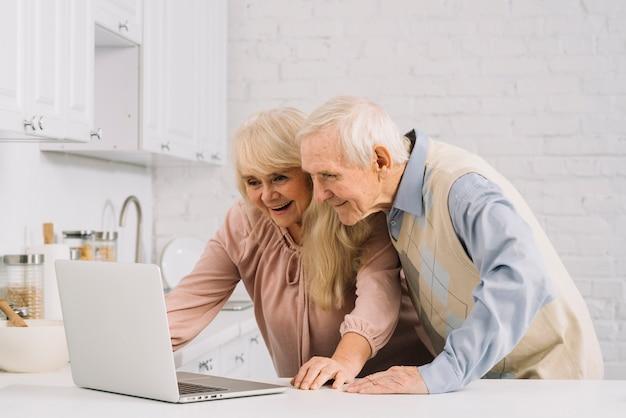 Hoger paar met laptop in keuken Gratis Foto