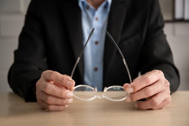 Hogere aziatische manager in zwarte kostuumzitting in het bureau en dichte omhooggaand van een oogglazen. Premium Foto