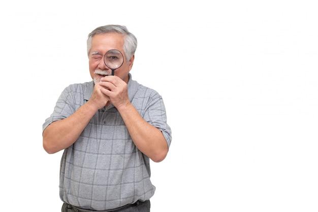 Hogere aziatische mens die door vergrootglas en glimlachen kijken die op witte muur wordt geïsoleerd Premium Foto