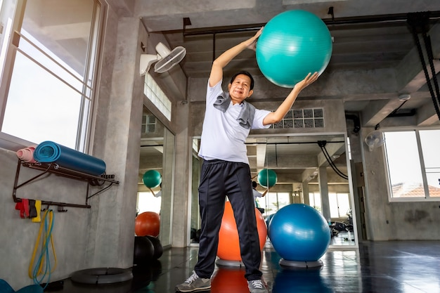 Hogere aziatische mens die in sportkleding buikspieren met balgymnastiek opleiden bij geschiktheid. Premium Foto