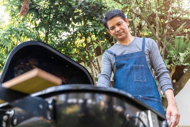 Hogere aziatische mens die schort draagt en een barbecuepartij in het park heeft. Premium Foto