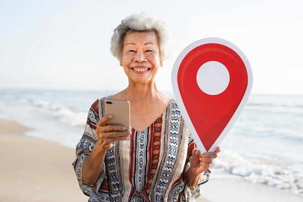 Hogere Aziatische vrouw die bij het strand controleert Gratis Foto