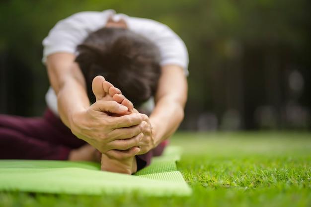 Hogere aziatische vrouw het praktizeren yogaoefening openlucht in de ochtend. senior gezonde levensstijl Premium Foto